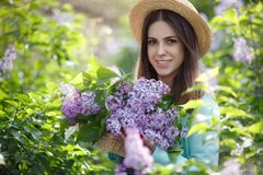 Spring portrait of a beautiful woman outdoors in the park, among the bushes blooming lilac. Young beautiful woman enjoying the smell of blooming lilac on a sunny royalty free stock photos