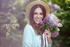 Spring portrait of a beautiful woman outdoors in the park, among the bushes blooming lilac. Young beautiful woman enjoying the smell of blooming lilac on a sunny royalty free stock image