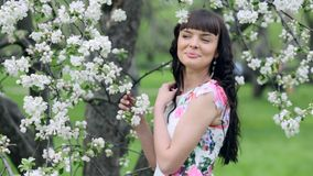 Young beautiful woman enjoying smell of blooming tree on a sunny day stock video footage