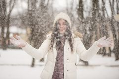 Young beautiful woman is enjoying the snow scattering it in the air, positive emotions, joy and happiness. Winter outdoor. Activities royalty free stock photos