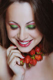 Young beautiful woman enjoying strawberries and smiling Stock Photo