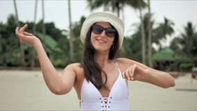 Young beautiful woman enjoying summer vacation and dancing on the beach.  stock footage