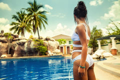 Young beautiful woman enjoying summer vacation on the tropical island Bali and enjoy holidays at swimming pool Stock Images