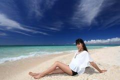 Young beautiful woman enjoying the sun on the beach royalty free stock photo