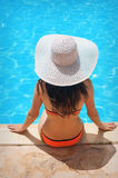 Young beautiful woman enjoying the sun and sitting on edge of the pool Stock Photo