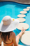 Young beautiful woman enjoying the sun and sitting on edge of the pool Stock Images