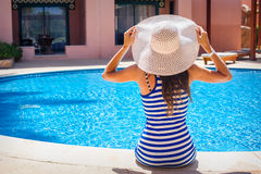 Young beautiful woman enjoying the sun and sitting on edge of the pool Royalty Free Stock Image