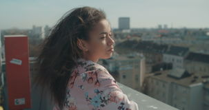 Young beautiful woman enjoying time on a rooftop and smiling to a camera. stock video footage