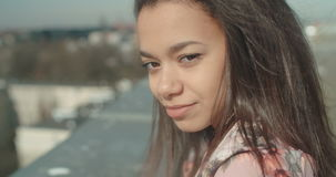 Young beautiful woman enjoying time on a rooftop and smiling to a camera. stock footage