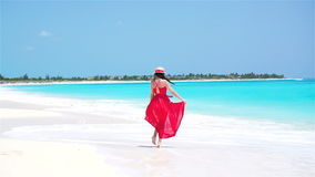 Young beautiful woman enjoying vacation on white tropical beach. Girl walking by the sea. Slow motion. Young beautiful woman during tropical beach vacation stock video