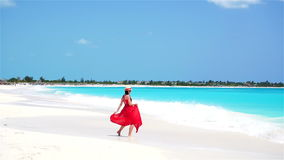 Young beautiful woman enjoying vacation on white tropical beach. Girl walking by the sea. Slow motion. Young beautiful woman during tropical beach vacation stock footage