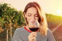 Young beautiful woman enjoying wine at vineyard. On sunny day royalty free stock photography
