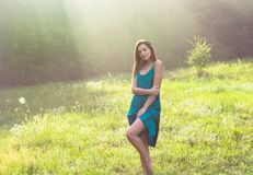 Young beautiful woman enjoys sunlight on a flower meadow at suns stock image