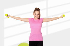 Young beautiful woman exercising with dumbells. Light background Stock Photos