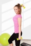 Young beautiful woman exercising with dumbells Stock Photos