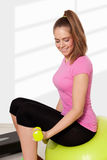 Young beautiful woman exercising with dumbells. Light background Royalty Free Stock Images