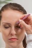 Young beautiful woman eyebrow plucking tweezers eyes hair Stock Photos