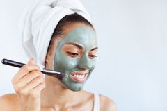 Young beautiful woman in face mask of therapeutic blue mud. Spa. Treatment, self care and healthy skin. Copy space, white background royalty free stock photos