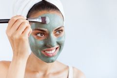 Young beautiful woman in face mask of therapeutic blue mud. Spa stock image
