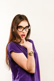 Young beautiful woman with facial expression of surprise standing over gray background. Wearing in trendy black dress. And glasses. Looking at the camera Royalty Free Stock Image