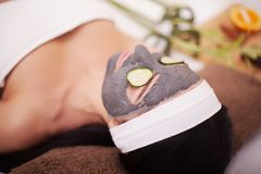 Young beautiful woman with facial mask of cucumber on her face lying at spa salon Stock Photography