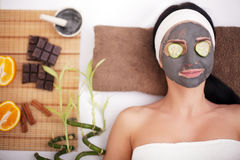 Young beautiful woman with facial mask of cucumber on her face lying at spa salon Stock Photo