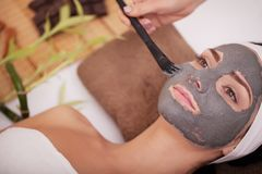 Young beautiful woman with facial mask, spa treatment.  Stock Photo
