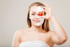 Young beautiful woman with facial mask and strawberry, spa treatment.  Royalty Free Stock Photography