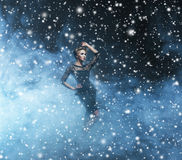 Young and beautiful woman in a fashion dress on a snowy background Stock Image