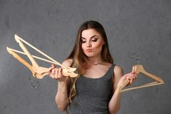 Young beautiful woman fashionable woman. Holding empty wooden hangers in her hand with smoother expression expressing nothing to wear from clothes and go to stock image