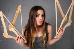 Young beautiful woman fashionable woman. Holding empty wooden hangers in her hand with smoother expression expressing nothing to wear from clothes and go to stock photos