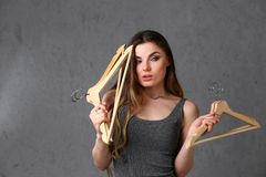 Young beautiful woman fashionable woman. Holding empty wooden hangers in her hand with smoother expression expressing nothing to wear from clothes and go to royalty free stock photos