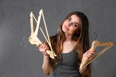 Young beautiful woman fashionable woman. Holding empty wooden hangers in her hand with smoother expression expressing nothing to wear from clothes and go to royalty free stock images