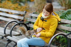 Young beautiful woman feeding a squirrel Royalty Free Stock Photo