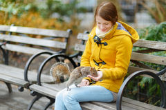 Young beautiful woman feeding a squirrel Royalty Free Stock Images