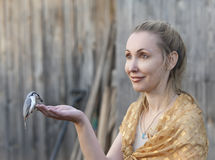 The young beautiful woman feeds a bird from a hand Stock Photography