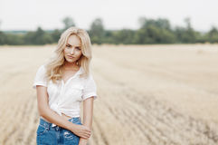 Young beautiful woman on field. Attractive young woman near the stacks of straw Royalty Free Stock Images
