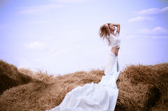 Young beautiful woman on field. Attractive young woman near the stacks of straw Royalty Free Stock Photo