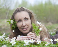 The young beautiful woman in the field of blossoming snowdrops in the early spring Stock Photography