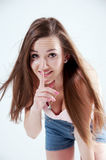Young beautiful woman with finger on her lips Royalty Free Stock Images