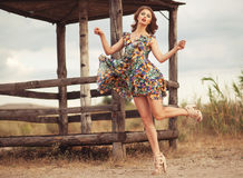 Young beautiful woman in flattering summer floral dress jumping. Over wooden fence Royalty Free Stock Photography