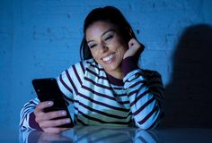 Young beautiful woman flirting and chatting on her smart phone late at night royalty free stock photo
