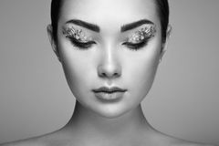 Young beautiful woman with flower makeup eyes Stock Photography
