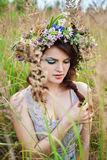 Young beautiful woman with flower wreath at the meadow Stock Image