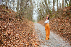 Young beautiful woman with flower wreath outdoors in the autumn park of fallen leaves Royalty Free Stock Photo