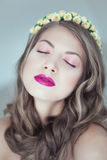 Young beautiful woman with flowers in hair and blue eyes Royalty Free Stock Photos