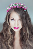 Young beautiful woman with flowers in hair and blue eyes Stock Images