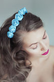 Young beautiful woman with flowers in hair and blue eyes Stock Image