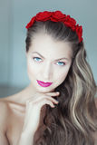 Young beautiful woman with flowers in hair and blue eyes Stock Photo