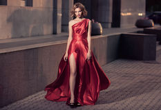 Young Beautiful Woman In Fluttering Red Dress. City Background. Royalty Free Stock Photos